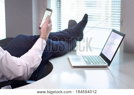 Successful business going well. Businessman laying in office with feet on table while income is rising and getting easy money. Stock market going up. Entrepreneur with smartphone and laptop in office.