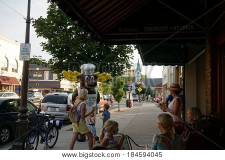 HARBOR SPRINGS, MICHIGAN / UNITED STATES - AUGUST 4, 2016: An entertainer in a moose costume greets visitors outside Kilwin's Candy Store, during the Street Musique event on Main Street in downtown Harbor Springs.