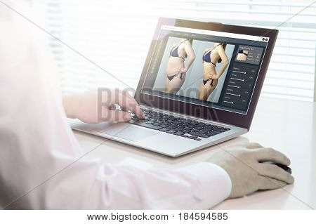 Photo editing with laptop and software. Retouching a photo of a girl in underwear for marketing or advertisement. Heavy image post processing and beauty standards concept.