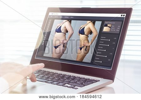 Professional man using laptop to transform chubby woman slim. Heavy photo editing with computer software. Standard of beauty, body image and post production concept.