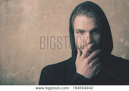 Caucasian man or young model hiding unshaven face with hand wearing fashionable grey hoodie hooded sweatshirt with hood on head on beige concrete wall. Secrecy and mystery copy space