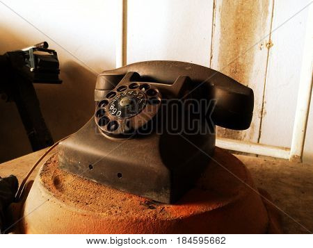 Black antique vintage analog telephone dialing or scrolling phone on wooden table,Contact us concept.