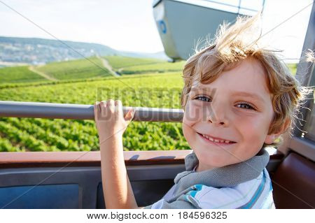 Smiling happy blond littlekid boy in cable funicular over vineyards in summer or autumn. Cute child enjyoing the view. Germany, vineyard near Mosel and Rhine.