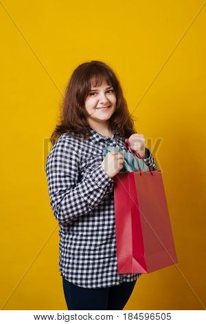 Happy plus-sized woman holding colored shopping bags over the yellow background.