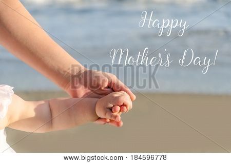 Happy Mother's day background with Mother's and child's holding hands on the sandy beach near ocean