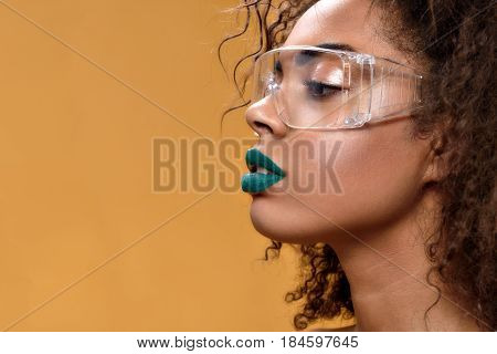 My defense. Side view of pretty ethnic woman with green lipstick posing with copy space in left side
