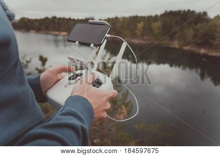 A man stands on the edge of a cliff above a beautiful lake in a pine forest and holds a remote control from the copter in his hands. Control of the flight of the Copter over the forest and lake