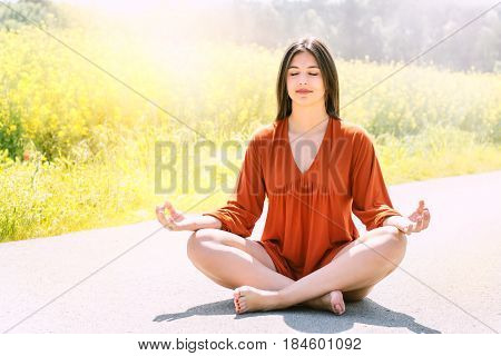 Portrait of young woman meditating in flower field. Girl sitting with eyes closed on road against bright yellow flower field.
