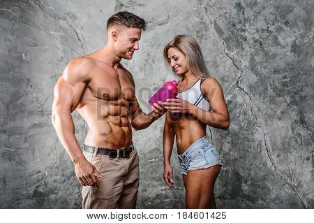 Pretty caucasian fitness girl and man on diet resting after exercise And drinking protein powder from shaker in the studion
