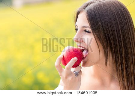 Close up face shot of Young woman biting red apple outdoors.