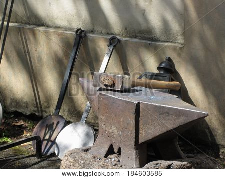 Blacksmith hammer resting on the anvil . Photo taken during outdoor public event (no ticket required) in public place . Pistoia Italy