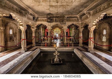 Udaipur castle courtyard with columns and fountain, India.