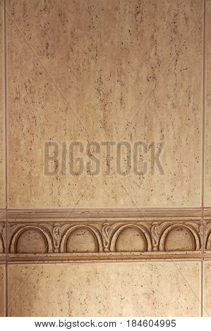 Closeup image of beige wall with frieze indoors for background pattern