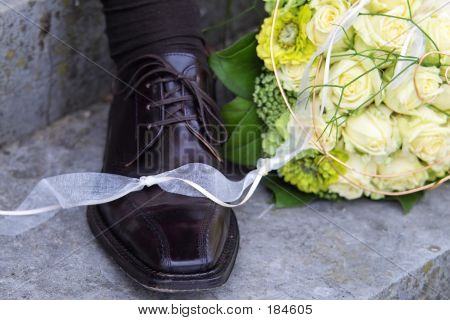 groom's boot with the bride's bouquet poster