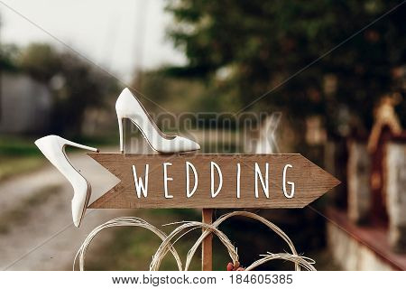 Beautiful White Shoes On Wooden Arrow With Wedding Text Sign. Rustic Wedding Concept. Pointing For W