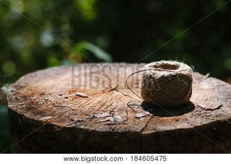 Close up skein of twine lying on a tree stump