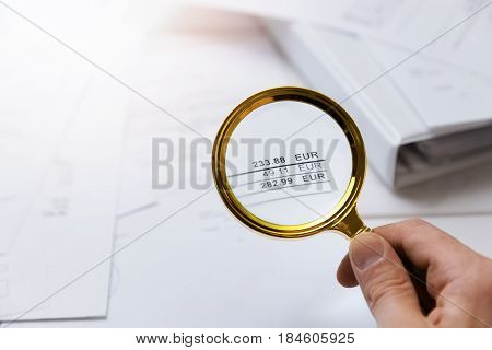 audit concept - auditor checking bills with magnifying glass