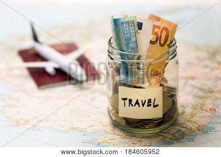 travel budget concept money savings in a glass jar on a map