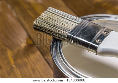Paint brush on a tin can with white paint close-up, against a background of a wooden texture of a table
