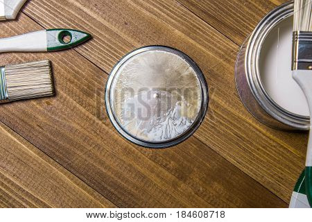 A set of white paint brushes, a metal can with white paint on a wooden table