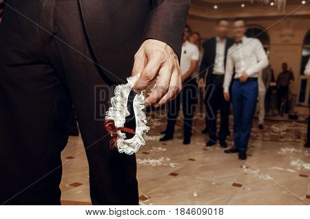Groom Holding Silk Garter From Bride At Wedding Party. Tradition Of Throwing Bridal Garter To Man, H