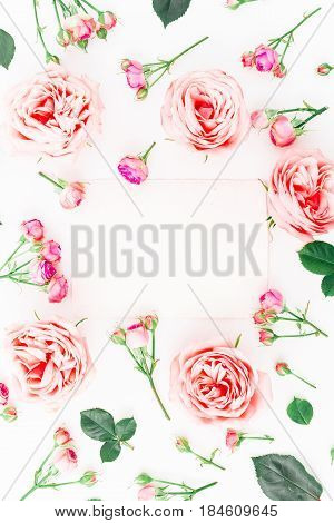Floral frame made of pink roses, buds and leaves on white background. Flat lay, top view. Floral pattern.