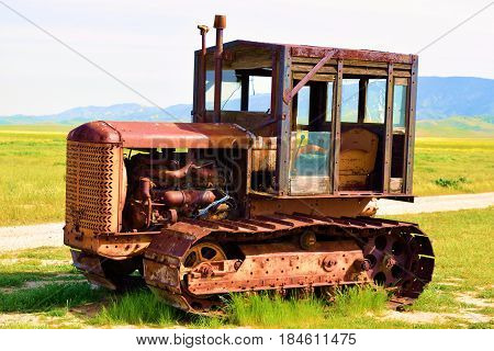 April 12, 2017 in Carrizo Plain, CA:  Rusty vintage forgotten tractor on a rural prairie landscape taken in the Carrizo Plain, CA where people can observe rural grasslands, abandoned ranches, and vintage farming equipment