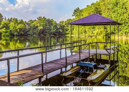 Footbridge with a gazebo and small pier for pleasure pedal catamaran on the lake shore. Dock for pedal boat and a quiet holiday in nature.