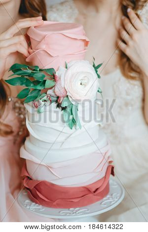Two tender bride girls models in Veil Wedding Dress holding beautiful wedding cake with fresh flowers. Image in pink beige pastel colors background. Boudoir photography. Selective focus. High key