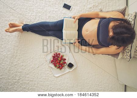 Young Pregnant Woman, Lying In Bed With Smartphone, Book, Coffee And Fruits,