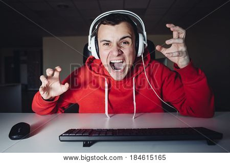 Crazy young man plays a game at home on your computer. Emotional gamer angry because he was killed in Computer game