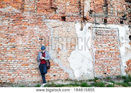 Handsome senior man in gray jacket holding smart phone, texting. Orange brick wall background.