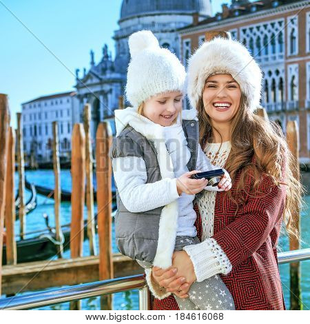 Mother And Child Travellers In Venice Viewing Photos On Camera
