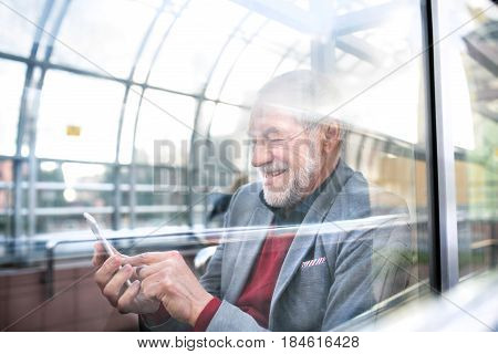 Handsome senior man in gray jacket holding smart phone, texting. Glass ceiling background. View through glass.