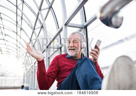 Handsome senior man holding smart phone, headphones on his ears, listening music, sitting in glass passage.