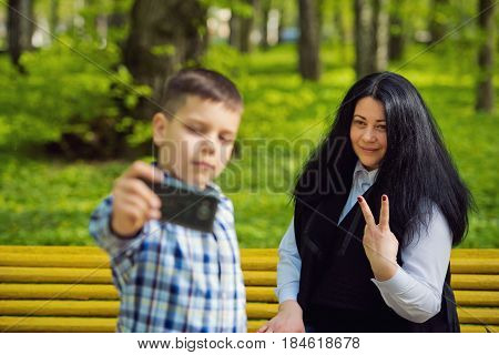 Little boy photographing his mother on a mobile phone in the park. Selective focus on the Mom. Family photo session.