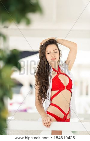 Vacation woman relaxing on beach in arbour on summer holidays resort. Beautiful happy multiracial Asian Chinese Caucasian young woman in swimsuit.