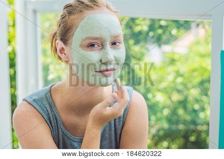 Spa Woman Applying Facial Green Clay Mask. Beauty Treatments. Close-up Portrait Of Beautiful Girl Ap