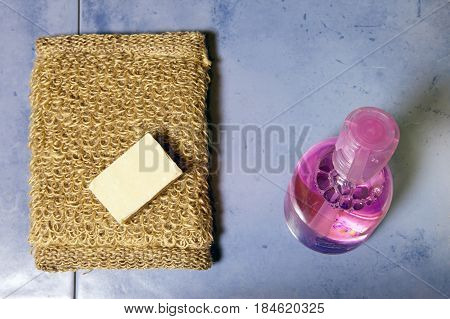 bast soap and bottle of gel on a tile flat lay