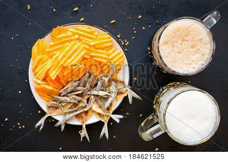 Dark And Light Beer With Chips And Dried Fish On A Black Background
