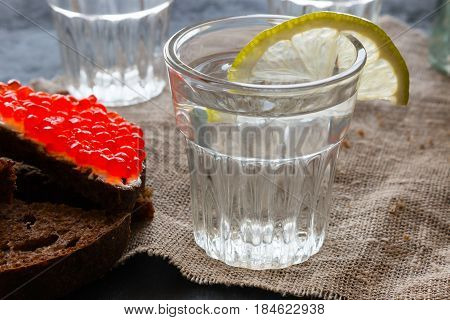 Glass Of Vodka With A Lemon Slice Close-up And Sandwich With Red Caviar