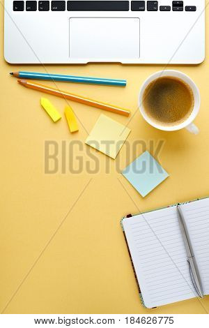 Start of Morning work office desk with a cup of coffee computer laptop pencil Sheet paper notebook pen yellow texture table Business concept background vertical