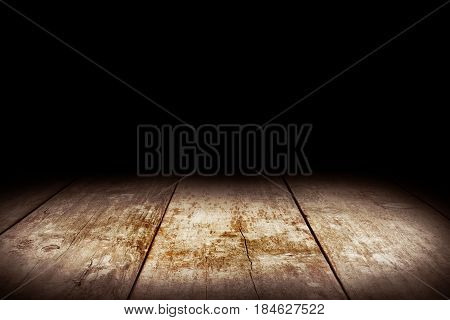 Wood table and black wall background, Empty wooden floor space platform with library background for product display.