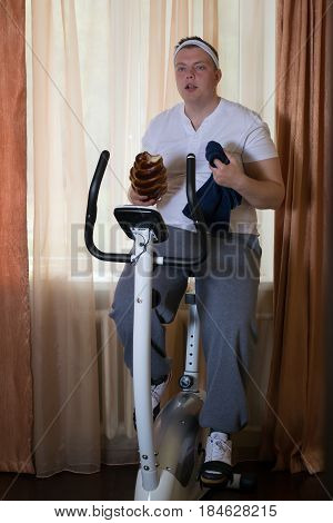 Fat guy exercising on stationary training bicycle and eating a bun at home