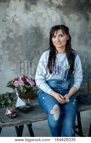 female in gray blouse and jeans make a bouquet over gray background putting roses in vase flowers and vase on wood table workplace
