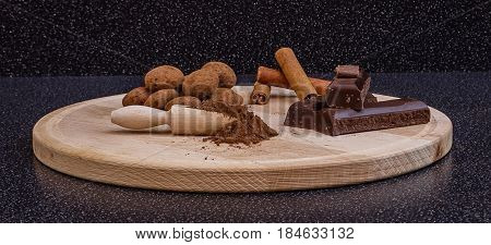 Cocoa truffles,cocoa powder,chocolate and cinnamon sticks on a wooden plate on black background