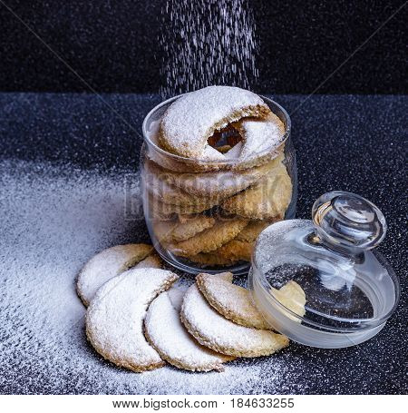 Homemade half-moon shaped cookies in a glass jar with sprinkled powdered sugar on black background