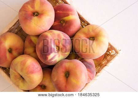High angle view of a basket of vine peaches also know as donut peaches