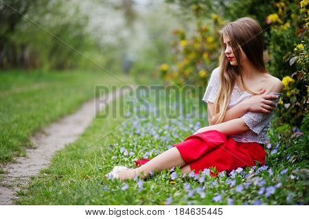 Portrait Of Sitiing Beautiful Girl With Red Lips At Spring Blossom Garden On Grass With Flowers, Wea