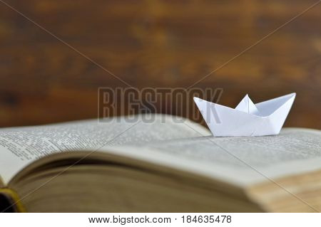 Close up of paper boat on the old book